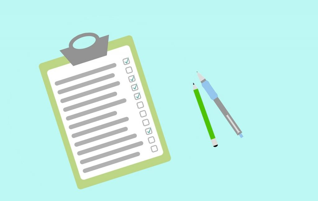 checklist on clipboard with pens